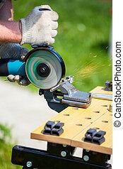 Man using angle grinder to cut metal bar