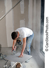 Man using angle grinder to cut tile