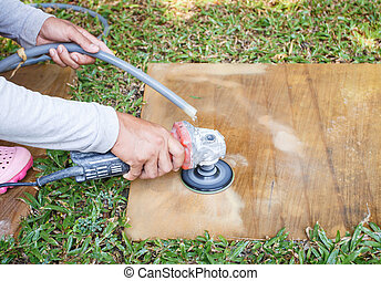 Man using angle grinder to grinding on sandstone