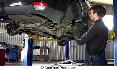 Man using big spanner to unscrew rusty bolts of brake system.