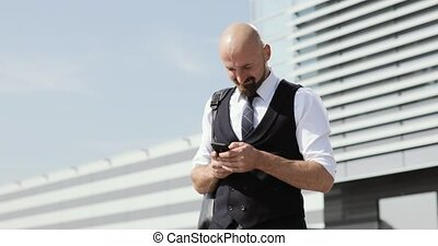 Man using business app on smart phone walking in city. Handsome young businessman communicating on smartphone smiling confident