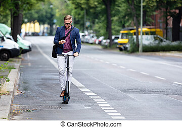 Man Using Cell Phone On Electric Scooter