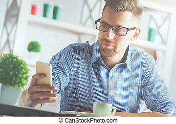 Handsome young man using cellphone at workplace