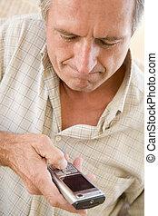 Man using cellular phone indoors