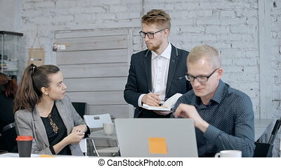 Man using computer while two manager discussing project -...