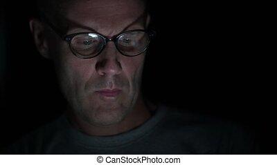 Man using digital tablet at night