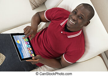 Happy Young African Man Sitting On Couch Using Digital Tablet