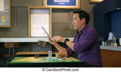 Man using digital tablet in cafe 4k - Young man using...