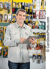 Man Using Digital Tablet In Hardware Store