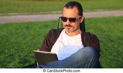 Man using digital tablet in park