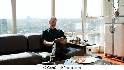 Man using digital tablet on sofa 4k - Man using digital...