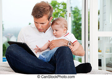 Man Using Digital Tablet while Holding Child - Father ...