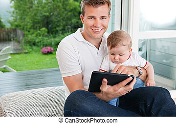 Man using digital tablet with child
