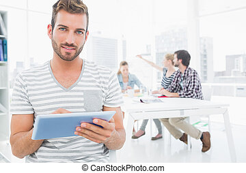 Man using digital tablet with colleagues in background