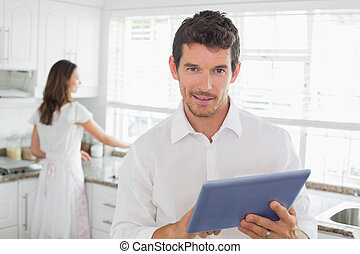 Man using digital tablet with woman in background in kitchen