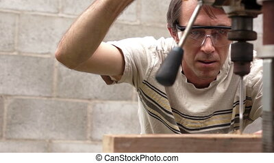Man Using Drill Press On Wood Board