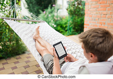 Man using e-book with lorem ipsum text on screen while relaxing in a hammock.