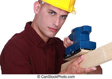 Man using electric sander