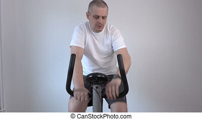 Man using exercise bike and looks at his watch