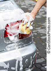 Man using foam for cleaning car