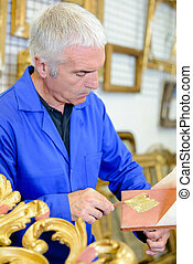 Man using gold leaf to restore an object