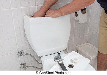 Man using hands repairing toilet cistern