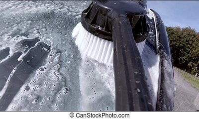 Man using high pressure washer and brush to clean car and wheels