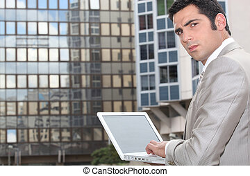 Man using his laptop outside an office block