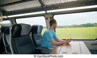 Man using his mobile phone in the train - Man using his...