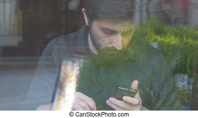 Man using his smartphone in cafe