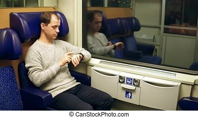 Man using his smartwatch in a train. Modern wearable device technology.