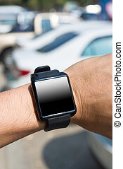 man using his smartwatch in parking car. Close-up hands