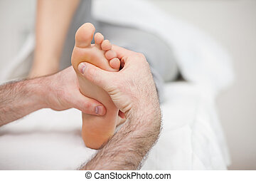 Man using his two hands to massage a foot