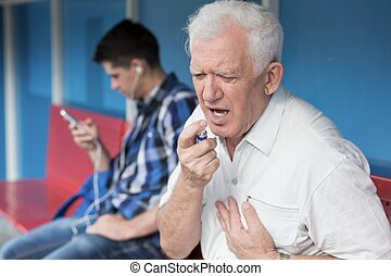 Man using inhaler - Senior man with chest pain using inhaler