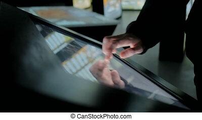 Man using interactive touchscreen display at modern history...