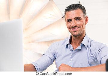 Man using laptop and looking at camera