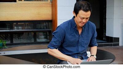Man using laptop at outdoor cafe 4k - Attentive man using...