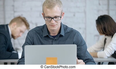 Focused and concentrate businessman or employee person sitting in office with modern interior room. Man using personal laptop or computer and creative new business application program online
