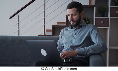 Man using laptop computer and working distant sitting at...