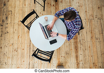 Man using laptop computer in cafe