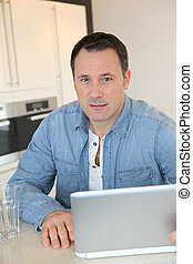 Man using laptop computer in kitchen