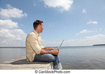 Man using laptop computer on a pontoon