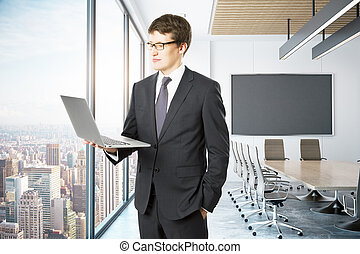 Man using laptop in conference room