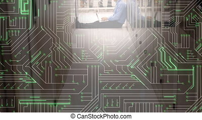 Man using laptop in server room and glowing circuit board