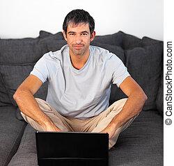 Man using laptop looking at camera