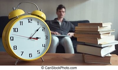 Man using laptop sitting on couch reading book at home. Yellow clock is ticking