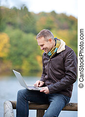 Happy mature man using laptop while sitting on fence