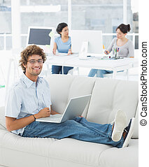 Man using laptop with colleagues at