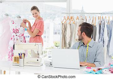 Man using laptop with fashion designer working at studio
