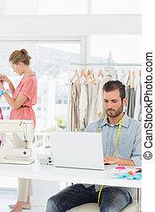 Man using laptop with fashion designer working at the studio